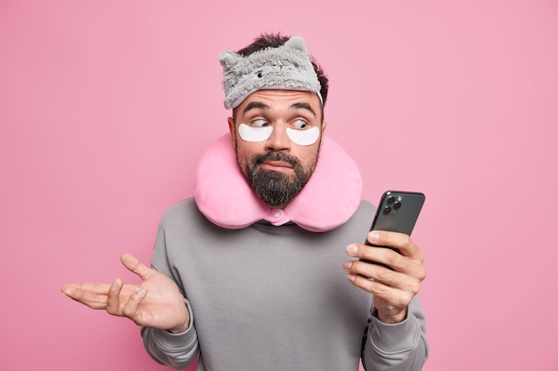Man shrugs shoulders holds mobile phone checks newsfeed wears blindfold neck pillow patches under eyes