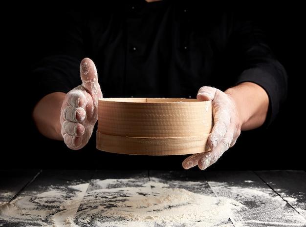Man sifts white wheat flour through a wooden sieve