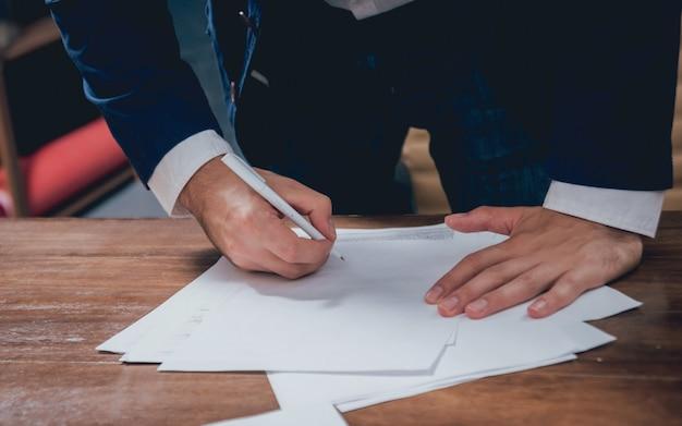 男は住宅ローンの住宅保険に署名します。契約署名前の顧客との不動産業者。