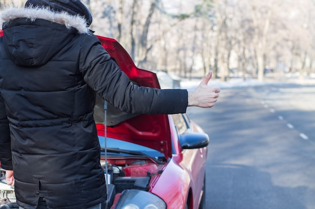 Man signaling problems with broken car on winter road.