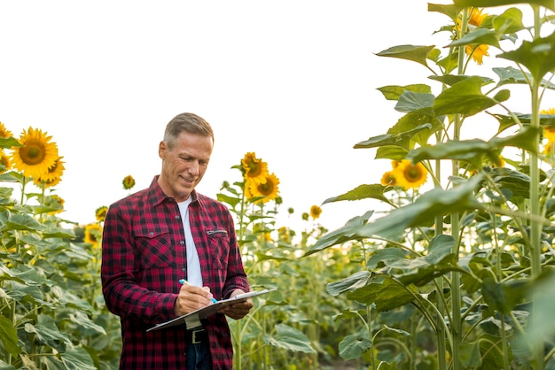 Man signing on a clipboard in a field