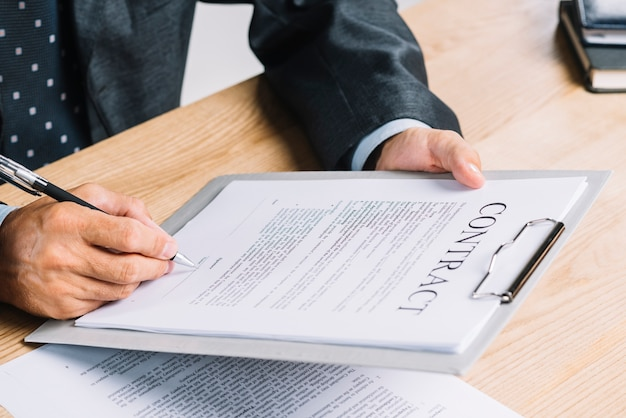 A man signing the contract paper attach on clipboard on the wooden table