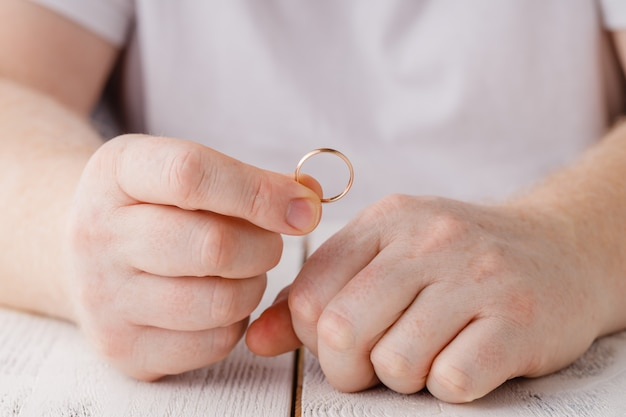 Man signing divorce decree and taking off wedding ring, copy space, blurred space