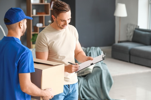 Man signing documents to confirm receiving of order from delivery company Premium Photo