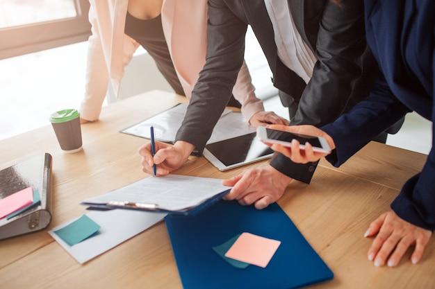 플라스틱 태블릿에 종이 서명하는 사람. 여자의 손을 잡고 전화. 다른 여자는 테이블에 기대다. 그들은 한 팀에서 함께 일합니다.