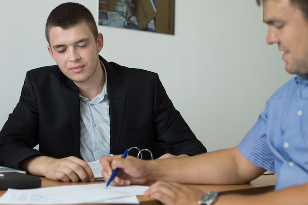 Man signing a purchase agreement under the watchful eye of a salesman or estate agent as he completes a transaction