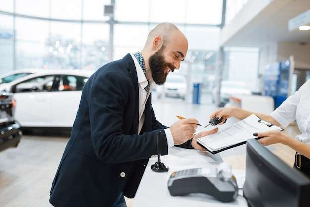 Мужчина подписывает контракт на покупку нового автомобиля в автосалоне. клиент и продавщица в автосалоне, мужчина, покупающий транспорт, автомобильный дилерский бизнес