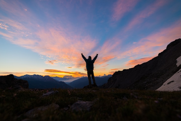 Man silhouette standing on mountain top outstretching arms, sunrise light colorful sky scenis landscape, conquering success leader concept.