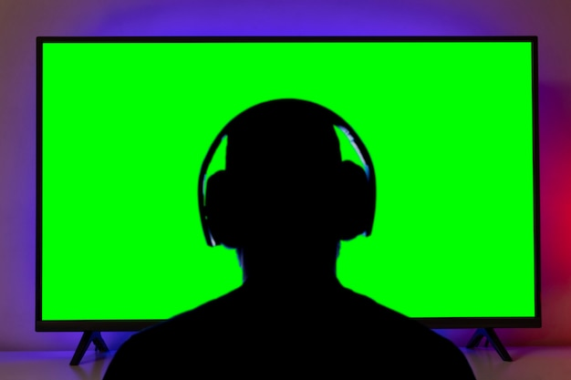 자르기 또는 클리핑을 위해 tv 앞에 헤드폰이 있는 남자 실루엣