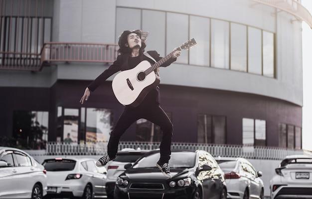 Человек поет песню и играет на гитаре на открытом воздухе