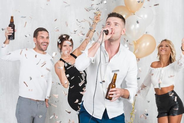 Man singing karaoke on party