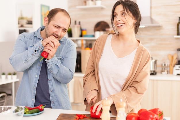 妻を笑顔にするキッチンで赤唐辛子で歌う男。サラダを準備しているガールフレンド。一緒に時間を過ごし、健康的な料理と笑顔で自宅で愛のカップルで面白い幸せ
