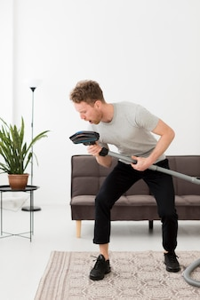 Man singing at vacuum while cleaning