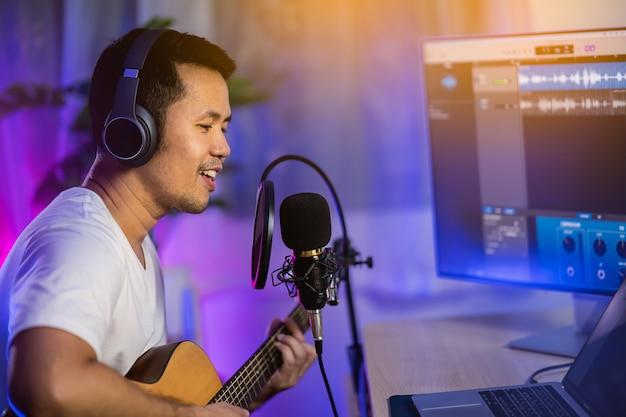 Мужчина поет в наушниках и играет на гитаре, записывает новую песню с микрофоном в домашней студии звукозаписи