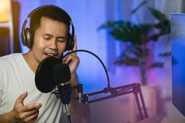 Мужчина поет в наушниках, записывает новую песню с микрофоном в домашней студии звукозаписи