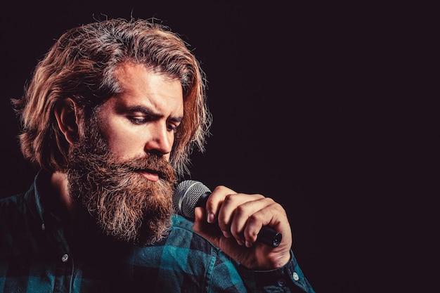마이크와 함께 노래 하는 남자. 마이크를 들고 노래하는 남성. 노래방에서 수염 난 남자는 마이크에 노래를 부릅니다. 남자는 노래방에 참석합니다. 마이크를 잡고 노래하는 수염을 가진 남자