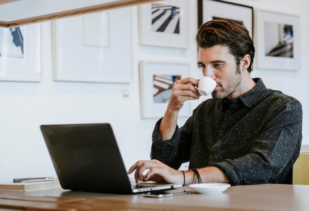 仕事中にコーヒーをすすりながら男