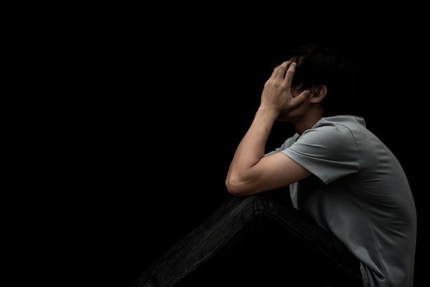 Человек сидит валяться грустно и беспокоиться на черном фоне