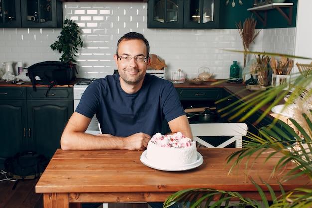 男はテーブルの上にケーキと一緒に家庭の台所に座っています。