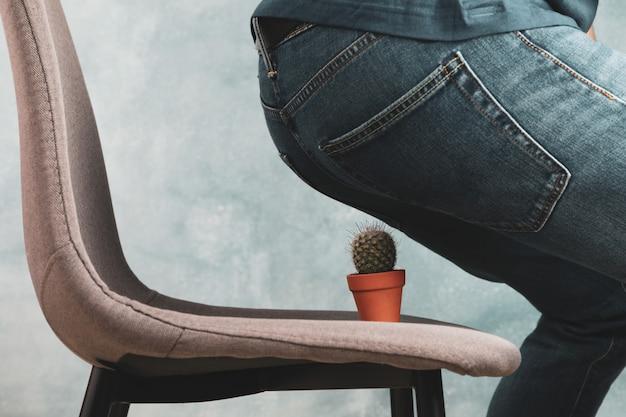 Человек сидит на стуле с кактусом. геморрой