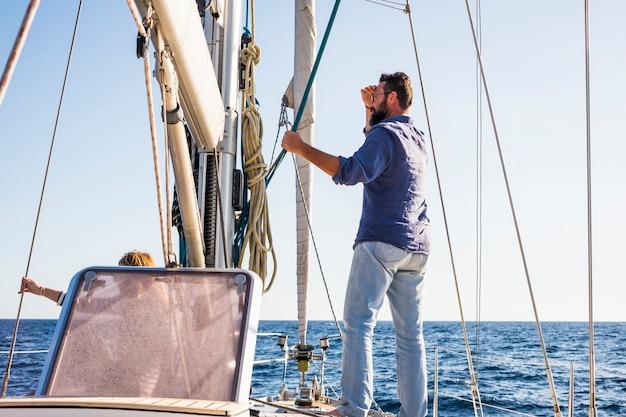 Человек сидит на парусной лодке, путешествует по океану и наслаждается свободным образом жизни
