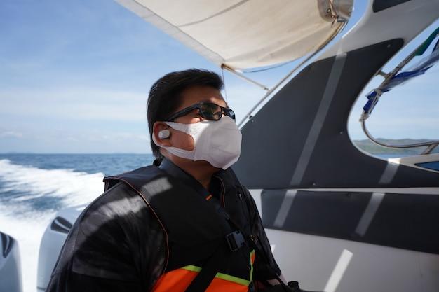 男はスピードボートに社会的距離を置いて座って救命ジャケットと保護フェイスマスクとイヤフォンを着用します