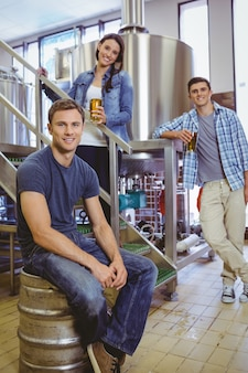 Man siting on keg and his colleague holding a glass of beer