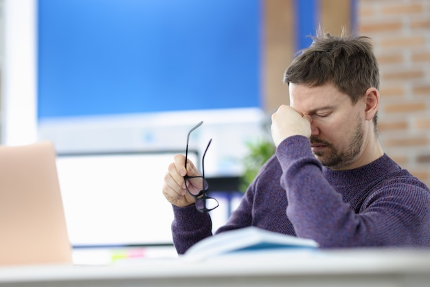 Man siting at table in office and holding bridge of his nose. eye fatigue when working at computer concept