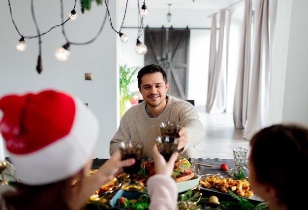 남자는 크리스마스 저녁 식사에서 테이블에 앉는다