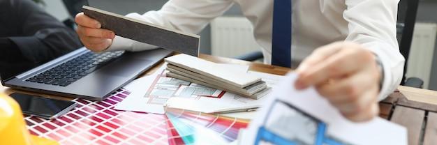 Человек сидит за столом с устройствами и цветовой схемой