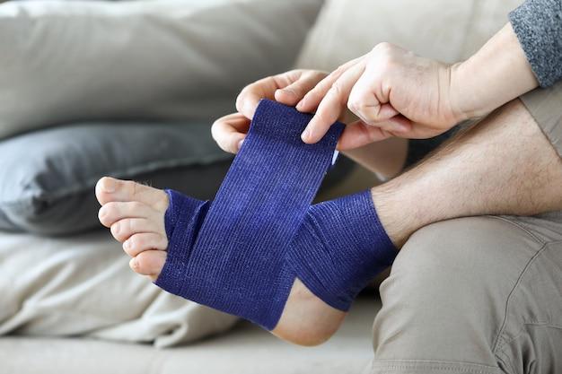 Мужчина сидит дома на диване и перевязывает ноги бандажом