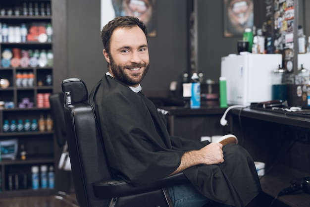 A man sits on barber's chair in man's barbershop