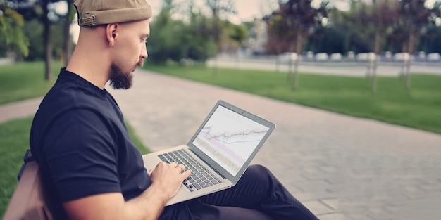 Man sits on the bench working uses laptop with graphics charts diagrams on screen stok traders