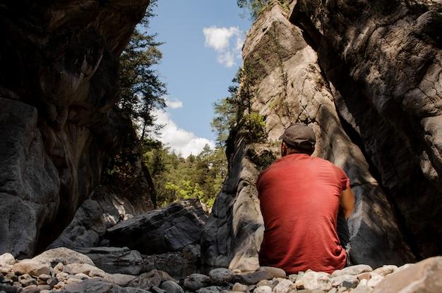 ギョイヌク渓谷の崖の間に座っている男