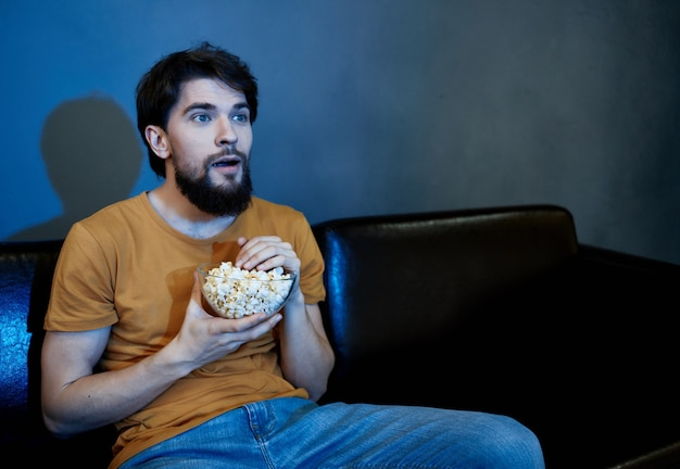A man sits on a black sofa with popcorn movie at night watching