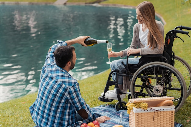 Man sits on a blanket and pours a woman a glass of champagne