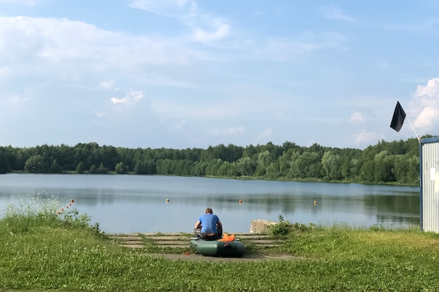Man sits on board an inflatable boat on the lake shore on a summer day