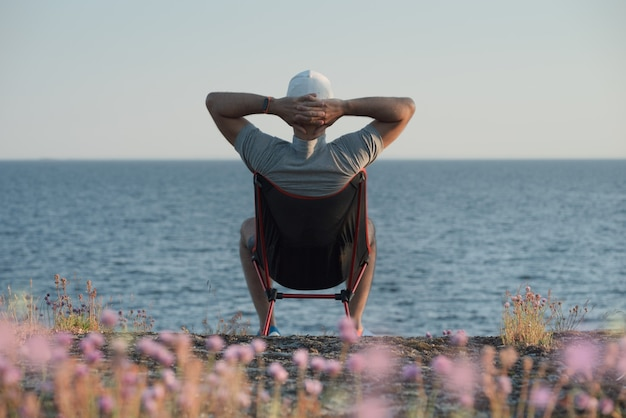 A man sits on a camping chair by the sea. he admires the landscape, his hands behind his head
