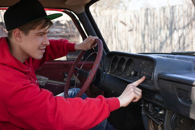 Man sits on driver's seat of retro car touching hand dashboard. purchase of the first car, vehicle, taxi