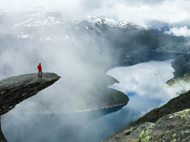 Man sits at the end of trolltunga before the mountains