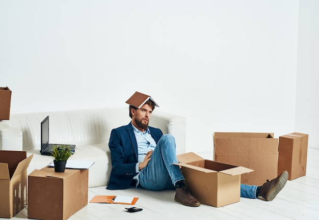 A man sits on the floor of a box with things unpacking emotions of an official businessman