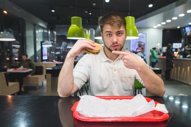 Человек сидит в бистро и показывает гамбургер в руках.