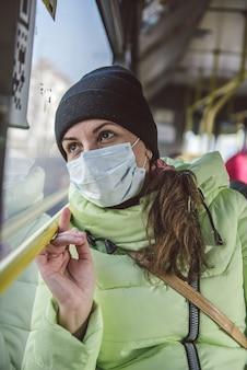 男は医療用保護マスクで市バスに座っています。公共交通機関におけるコロナウイルスcovid-19に対する保護。