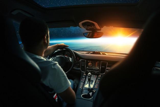 남자는 우주선 차에 앉아 우주에서 일몰과 함께 행성으로 날아갑니다. 자동차, 개념으로 우주 여행입니다. 운전석 뒤에 있는 운전자. 우주에서의 행성간 택시, 창의적인 아이디어