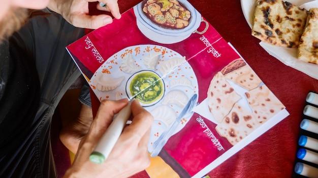 男はカフェに座っているし、アートマーカーでスケッチブックにインド料理の画像を描画