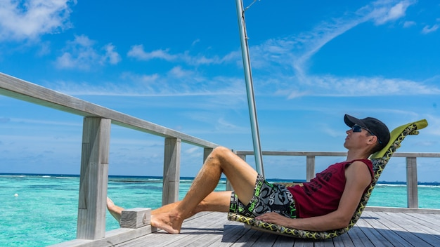 男はモルディブの高級アイランドリゾートの水上バーに座っています。