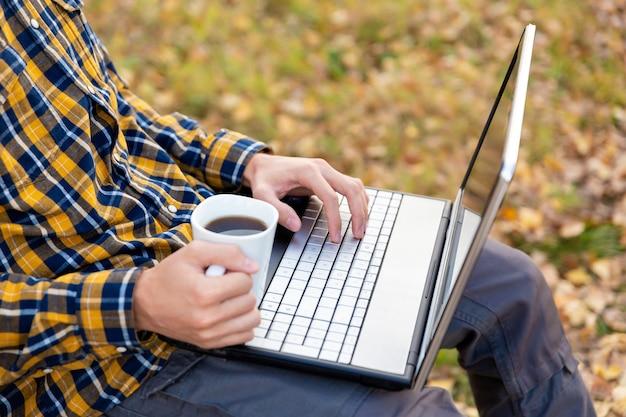 男は公園に座ってラップトップで作業しますキーボードで入力し、コーヒーのマグカップを持っている手
