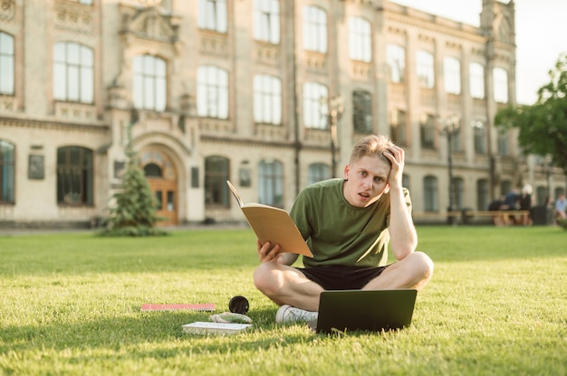Man sits on a lawn on a university campus with a laptop