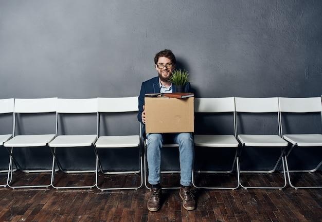 남자는 불만의 우울증을 무시하는 물건으로 의자 상자에 앉아있다.