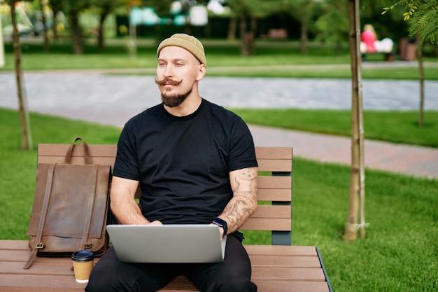 남자는 화면 스톡 트레이더에 그래픽 차트 다이어그램이 있는 노트북을 사용하여 작업하는 벤치에 앉아 있습니다.